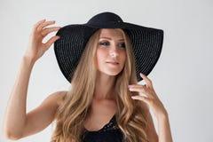 有蓝眼睛的白肤金发的女孩有一个边缘的一个帽子白色背景的 免版税库存照片