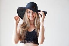有蓝眼睛的白肤金发的女孩有一个边缘的一个帽子白色背景的 库存照片