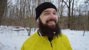 有蓝眼睛的笑在冬天森林里的有胡子的人特写镜头画象  股票视频
