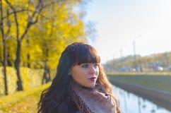 有蓝眼睛的美丽的女孩在秋天公园 免版税库存图片