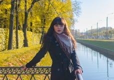 有蓝眼睛的美丽的女孩在秋天公园 库存图片