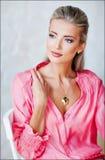 有蓝眼睛的美丽的性感的肉欲的白肤金发的女孩在一台桃红色起重器 免版税图库摄影