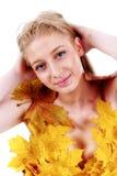 有蓝眼睛的美丽的金发碧眼的女人在叶子礼服  免版税库存照片