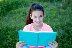 有蓝眼睛的美丽的青春期前的女孩读书的 免版税库存图片