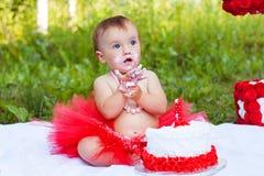 有蓝眼睛的美丽的婴孩吃生日蛋糕的 库存照片