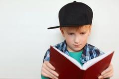 有蓝眼睛的逗人喜爱的小男孩在黑盖帽和被检查的衬衣读书的,为调查与se的书的教训做准备 库存照片