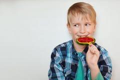 有蓝眼睛的逗人喜爱的白肤金发的男孩在控制中衬衣穿戴了舔棒棒糖的有看在旁边在白色背景的愉快的表示 免版税图库摄影