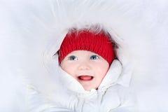 有蓝眼睛的逗人喜爱的笑的婴孩在雪衣服 免版税库存图片