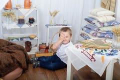 有蓝眼睛的闪光的小男孩笑和 有土气装饰的房子 免版税库存照片
