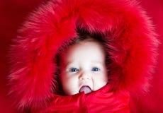 有蓝眼睛的滑稽的女婴在温暖的冬天起重器 库存图片