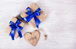 有蓝色丝带的两个礼物盒和从一棵树的心脏在白色木背景 日s华伦泰 复制空间 免版税图库摄影