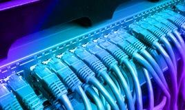 有蓝色互联网插接线的服务器机架缚住 免版税库存照片