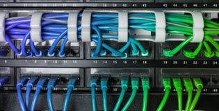 有蓝色互联网插接线的服务器机架缚住 库存照片