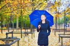 有蓝色伞的少妇在巴黎卢森堡庭院里在一个秋天或春天雨天 免版税库存图片