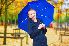 有蓝色伞的少妇在巴黎卢森堡庭院里在一个秋天或春天雨天 库存照片