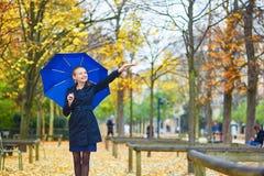 有蓝色伞的少妇在巴黎卢森堡庭院里在一个秋天或春天雨天 免版税库存照片