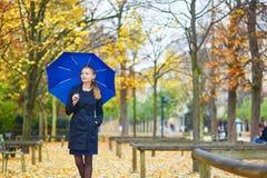 有蓝色伞的少妇在巴黎卢森堡庭院里在一个秋天或春天雨天 库存图片