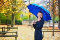 有蓝色伞的少妇在巴黎卢森堡庭院里在一个秋天或春天雨天 免版税图库摄影