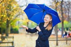 有蓝色伞的少妇在巴黎卢森堡庭院里在一个秋天或春天雨天 图库摄影
