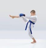 有蓝色传送带和覆盖物的男孩在手上打踢 图库摄影