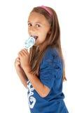 有蓝色吮吸者的逗人喜爱的棕褐色的深色的女孩 库存照片