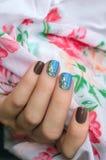有蓝色和灰色钉子艺术的妇女手 图库摄影