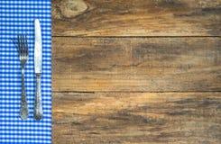 有蓝色和白色织品的老银色利器在土气木桌上 库存照片