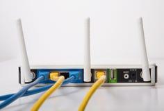 有蓝色和黄色缆绳的白色无线路由器 库存照片