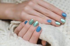 有蓝色和绿色闪烁钉子的美好的女性手设计 库存照片