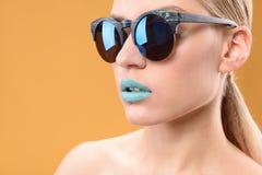 有蓝色唇膏的可爱的白肤金发的女孩 库存照片