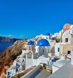 有蓝色圆屋顶的地方教会在Oia,圣托里尼,希腊, panoram 库存照片