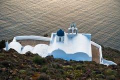 有蓝色圆顶的小白色教会在破火山口在日落的沿海,圣托里尼海岛 库存照片