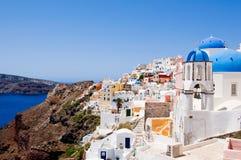 有蓝色圆顶的Oia教会和在圣托里尼,希腊海岛上的白色响铃  免版税库存照片
