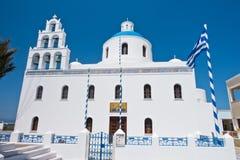 有蓝色圆顶的Panagia教会和在Oia村庄,圣托里尼海岛的大钟楼 免版税库存图片