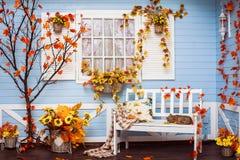 有蓝色墙壁和白色窗口的舒适乡间别墅在秋天 库存图片