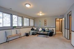 有蓝色墙壁和装壁板的舒适家庭娱乐室 图库摄影