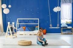 有蓝色墙壁的女孩卧室 免版税库存图片