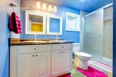 有蓝色墙壁的孩子卫生间和桃红色地毯和毛巾 图库摄影