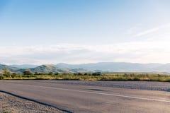 有蓝色夏天天空和小山的空的柏油路在背景 克里米亚, Koktebel 免版税库存照片