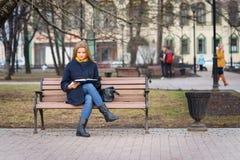 有蓝色外套的年轻欧洲妇女在公园读一些书,当她坐长凳在秋天时间时 库存图片