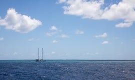 有蓝色多云天空的偏僻的风船 免版税库存照片