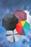 有蓝色多雨云彩的四把开放伞 免版税库存图片
