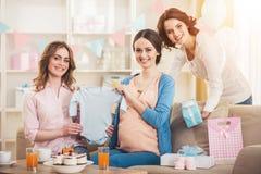 有蓝色婴儿连裤外衣和朋友的孕妇 免版税库存照片