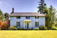 有蓝色屋外用的油漆和小开放门廊的美国二层楼的房子 免版税库存图片