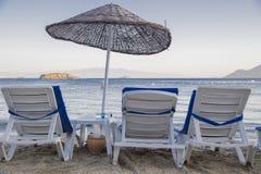 有蓝色床垫和海滩bamb的三个海滩轻便马车休息室 库存照片