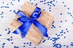 有蓝色弓的礼物盒在与闪闪发光的白色背景 库存照片
