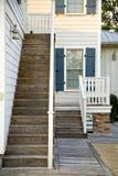 有蓝色快门和木台阶的白色房子 库存照片