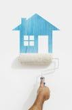 有蓝色房子标志绘画的漆滚筒手在墙壁上 免版税图库摄影