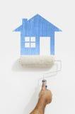 有蓝色房子标志绘画的漆滚筒手在墙壁上 免版税库存照片