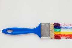 有蓝色把柄和彩虹刷子冲程的油漆刷 库存图片